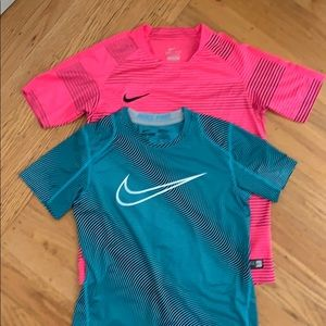Two Nike dri-fit short-sleeved shirts.